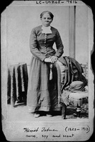 Harriet Tubman, full-length portrait, standing with hands on back of a chair
